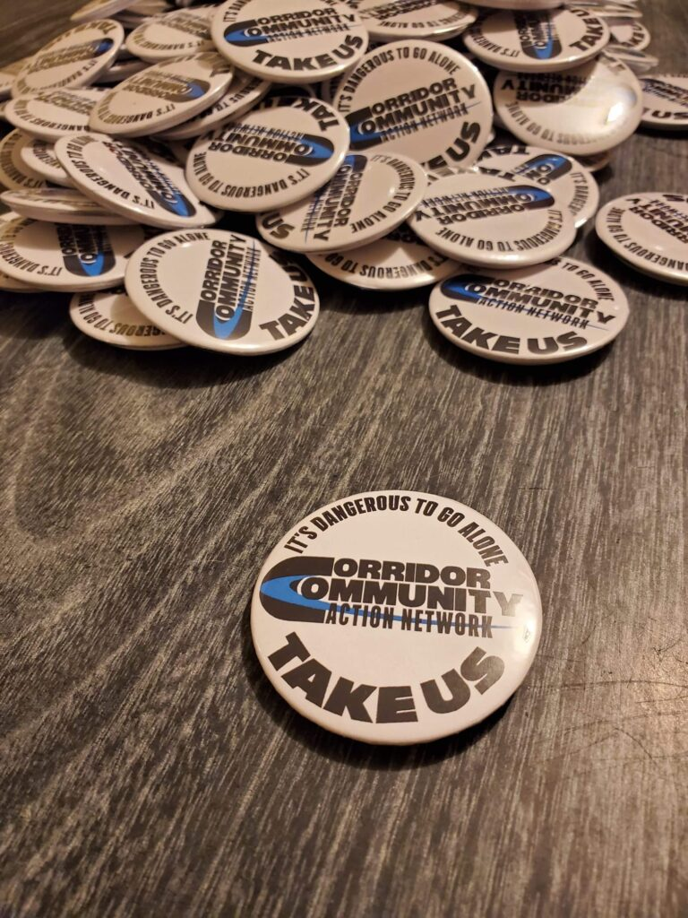 "Button on a table that reads ""It's dangerous to go alone, take us. Corridor Community Action Network."""
